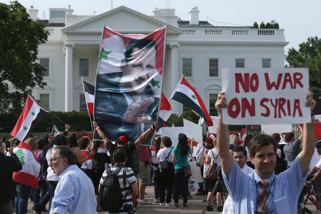 A banner bearing the image of Syrian President Bashar al-Assad is carried by some of the 200 people demonstrating in support of al-Assad and against a possible military attack on Syria by the United States outside the White House, September 9, 2013 in Washington, DC.