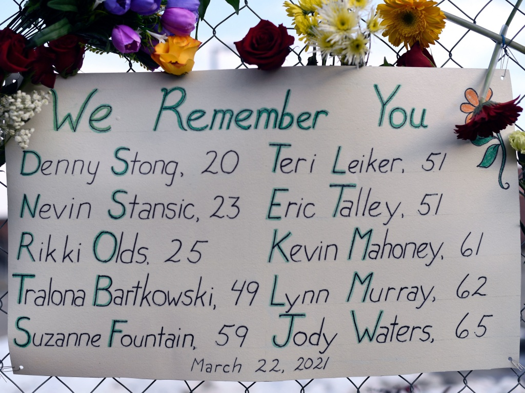 A sign framed with flowers lists the victims' names on the fence outside a King Soopers grocery store in Boulder, Colo. The suspected gunman made his first court appearance on Thursday.