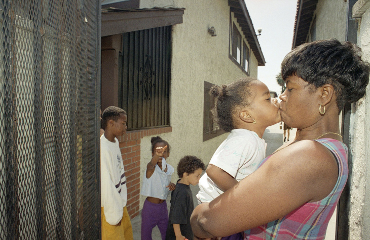 Elvira Evers holds her daughter, Jessica in front of the security gates of her apartment complex in Gardena, California, Monday, April 4, 1994 where she finally feels safe after moving from her previous residence in Compton, Calif. Evers was shot during the 1992 Los Angeles riots while pregnant with Jessica, who was born with the bullet in her elbow. In the background are son Marvin, 13, left, daughter Nella, 7, and Paris Beacon, a 5-year-old neighbor. (AP Photo/Rhonda Birndorf)