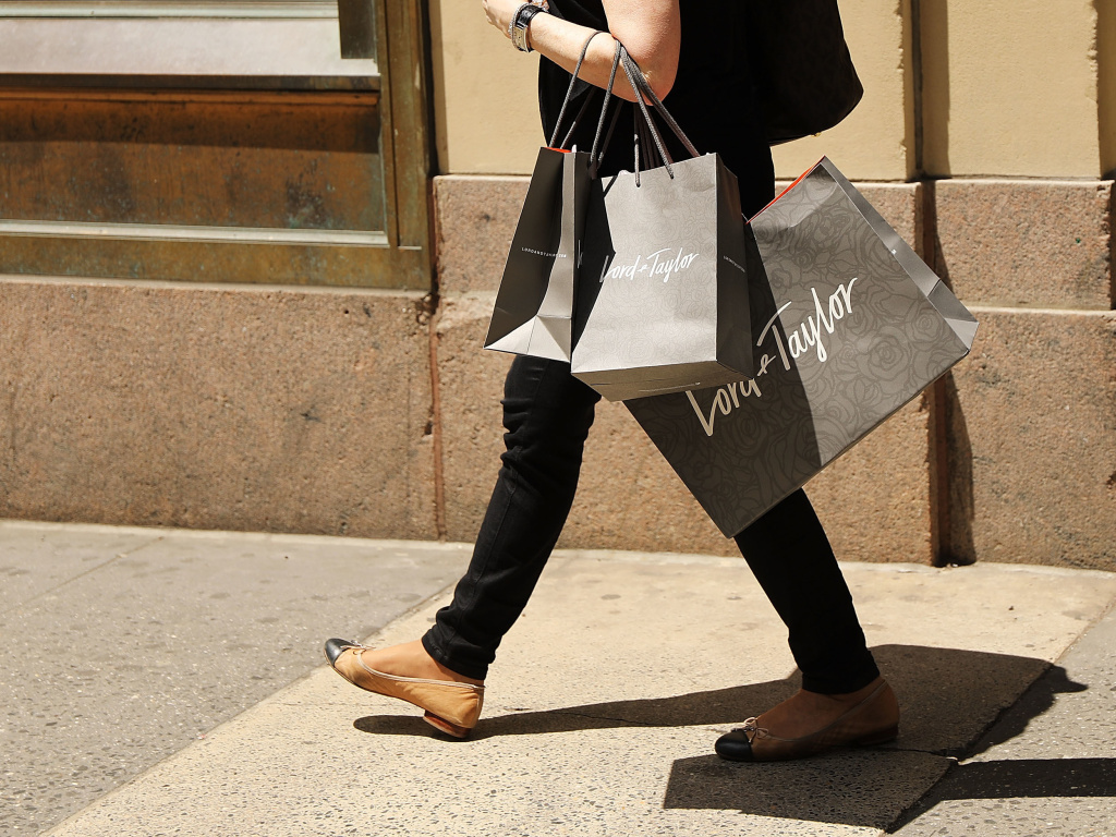 A woman walks out of Lord & Taylor's flagship store in Manhattan in June 2018, before the location was closed and the building was sold in 2019.
