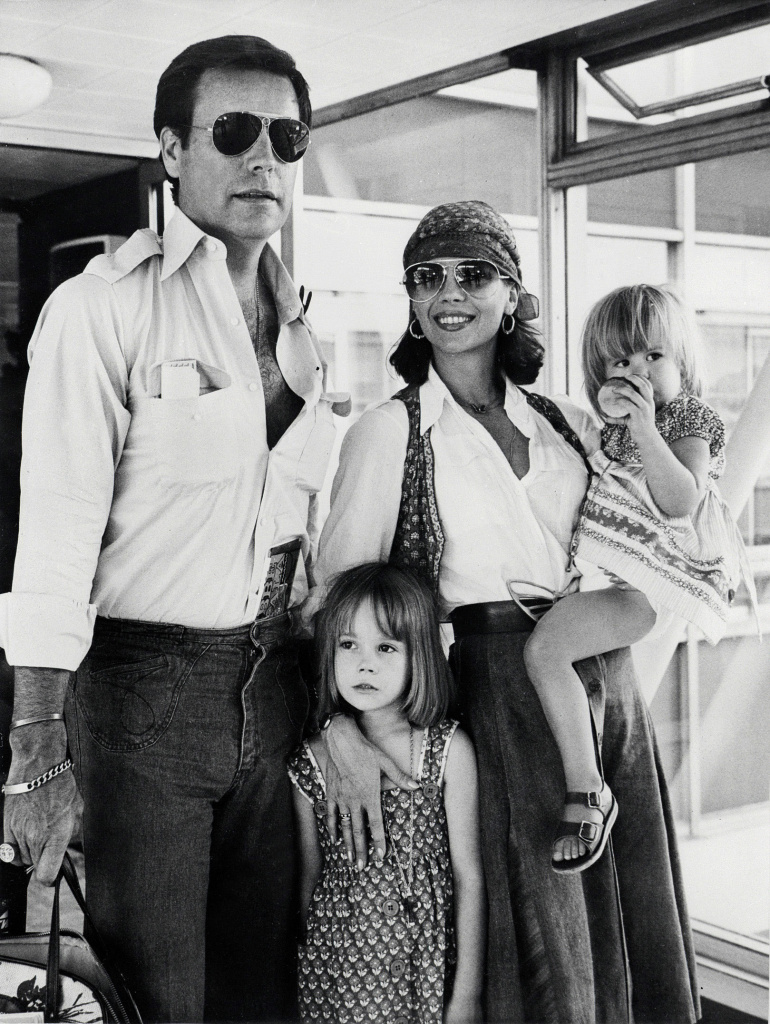 Robert Wagner and Natalie Wood arrive with her child Natasha (center) and their daughter Courtney (right) at London airport on July 4, 1976.