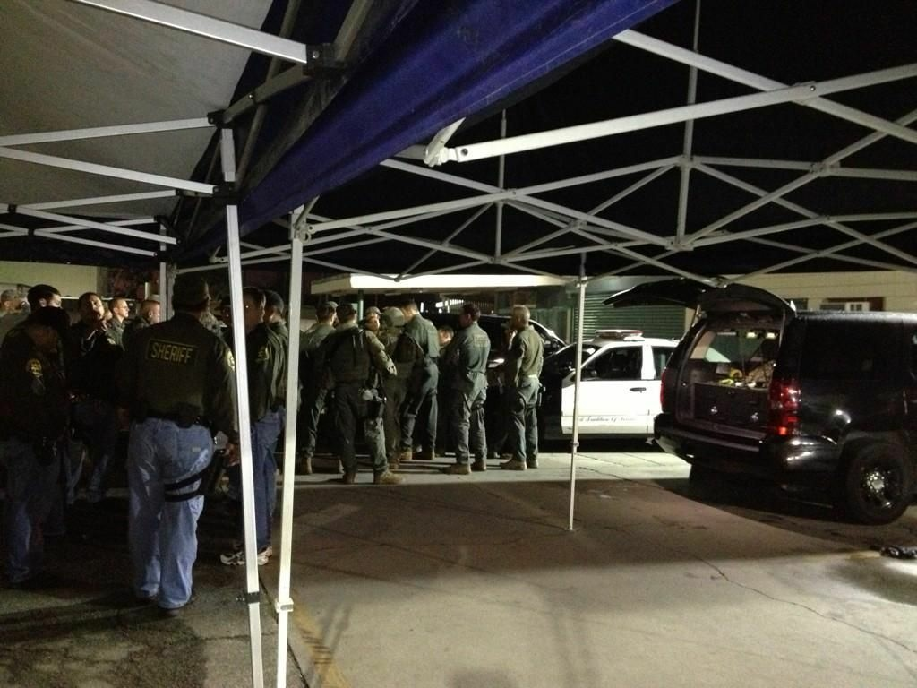 LASD deputies meet at a command post during a search for suspects who shot a deputy Friday night in the Florence area of South Los Angeles.