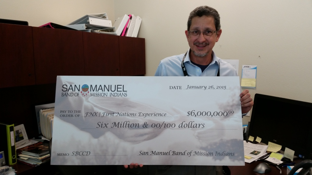 Alfredo Cruz, general manager of FNX and KVCR holds a check from the San Manuel Board of Mission Indians. The funds will support three years of programming and operations
