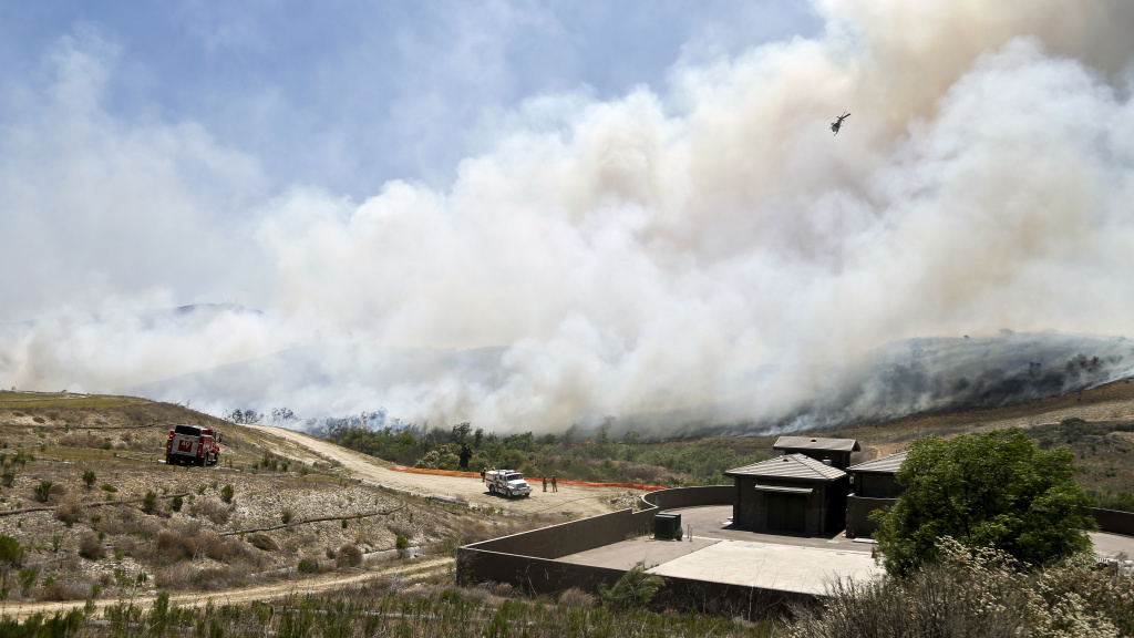 Smoke rises from a canyon where a wild fire burned Tuesday in San Diego. County officials say they're investigating how a rogue message appeared in their emergency app.