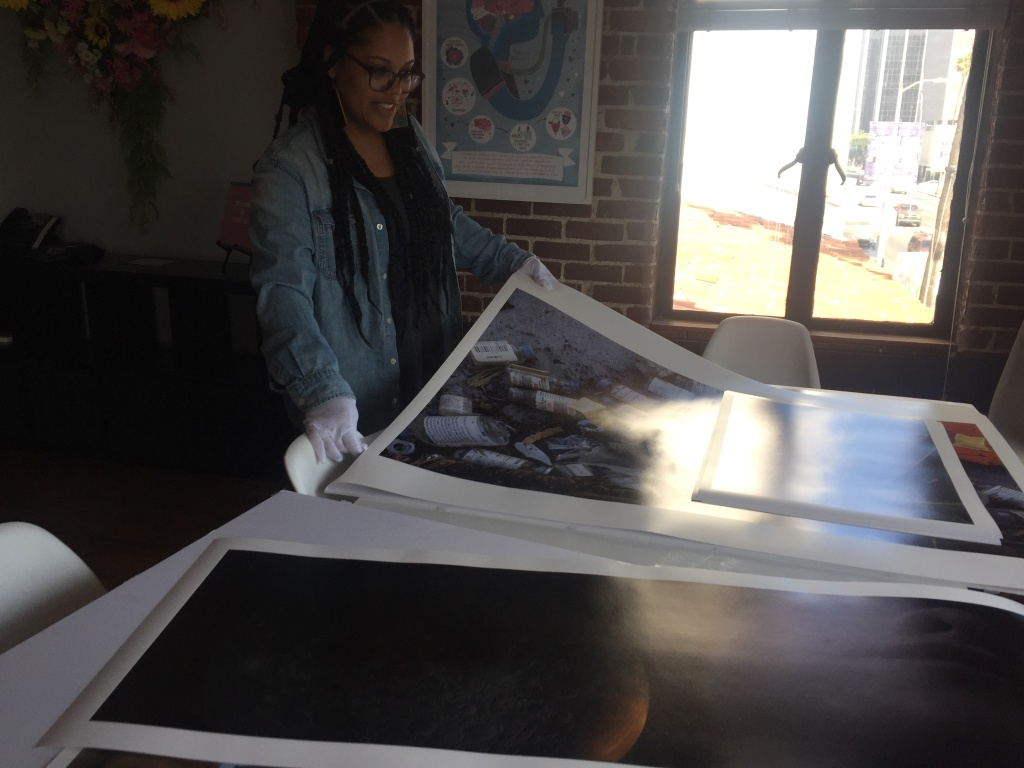 Pablove program manager and professional photographer Ashley Blakeney handles some of the prints in the foundation's Sunset Boulevard office ahead of the gallery show.