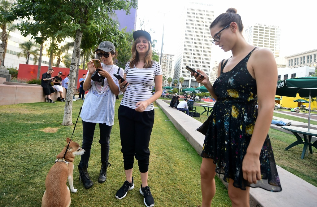 April O'Neil (L), Ariana Nussdorf (C) and Julia Voth (R)look at their cellphones while playing Pokemon Go at Pershing Square.