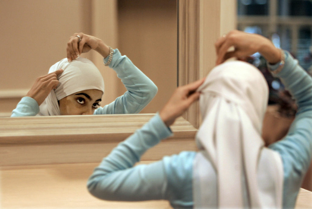 A woman adjusts her hijab, a head covering worn by female observant Muslims.