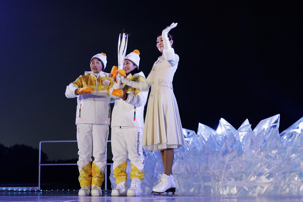 Olympic torch carriers pass the torch to figure skater Kim Yu-na before she lights the Olympic Cauldron during the Opening Ceremony of the PyeongChang 2018 Winter Olympic Games on February 9, 2018.