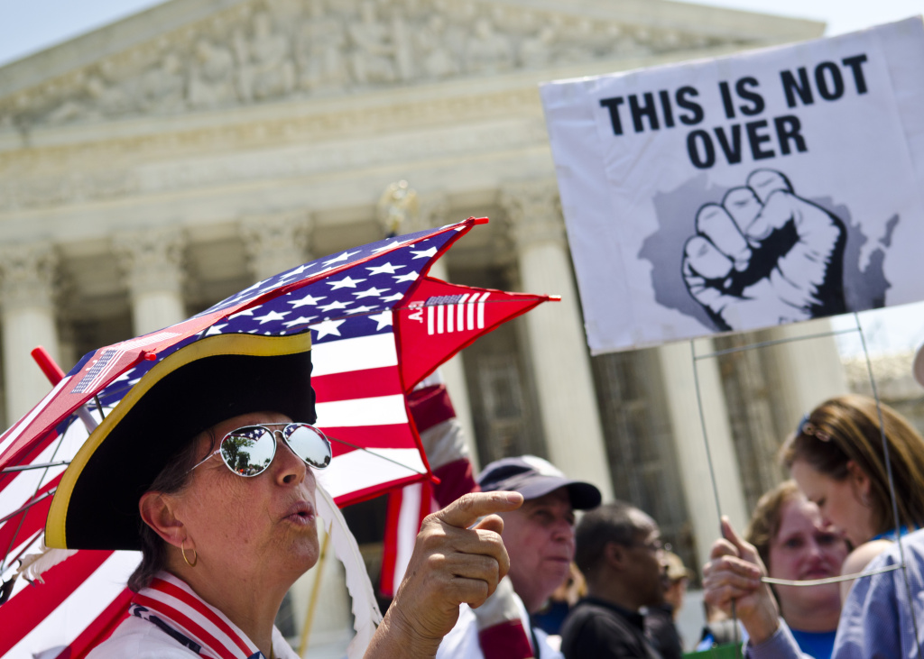 WASHINGTON, DC - JUNE 28:  Susan Clark argues with a another protester about the Affordable Healthcare Act outside the U.S. Supreme Court on June 28, 2012 in Washington, DC. The Court found the law to be constitutional and did not strike down any part of it. (Photo by Kris Connor/Getty Images)