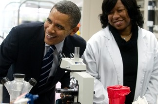 US President Barack Obama smiles after looking through a microscope as he tours a biotech classroom at Forsyth Technical Community College in Winston-Salem, North Carolina.