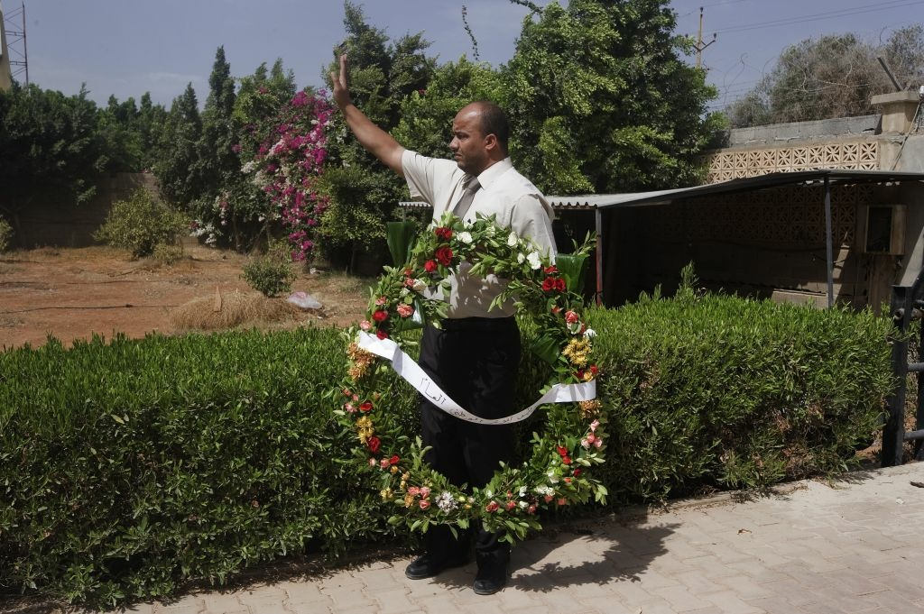 A Libyan man gestures as he holds a wreath of flowers to be placed by Mohamed al-Megaryef (unseen), president of Libya's highest political authority the General National Congress, inside the US consulate compound on September 14, 2012 in Benghazi, Libya, following an attack on the building late on September 11 in which the US ambassador to Libya and three other US nationals were killed.