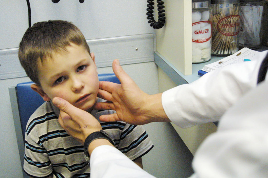 With a temperature of 103.8, Asa Moore, 6, of Vivian, Louisiana is examined at the North Caddo Surgical and Medical Center for symptoms of Influenza December 12, 2003 in Vivian, Louisiana. Moore had not received a flu shot and the medical center was out of the vaccine.