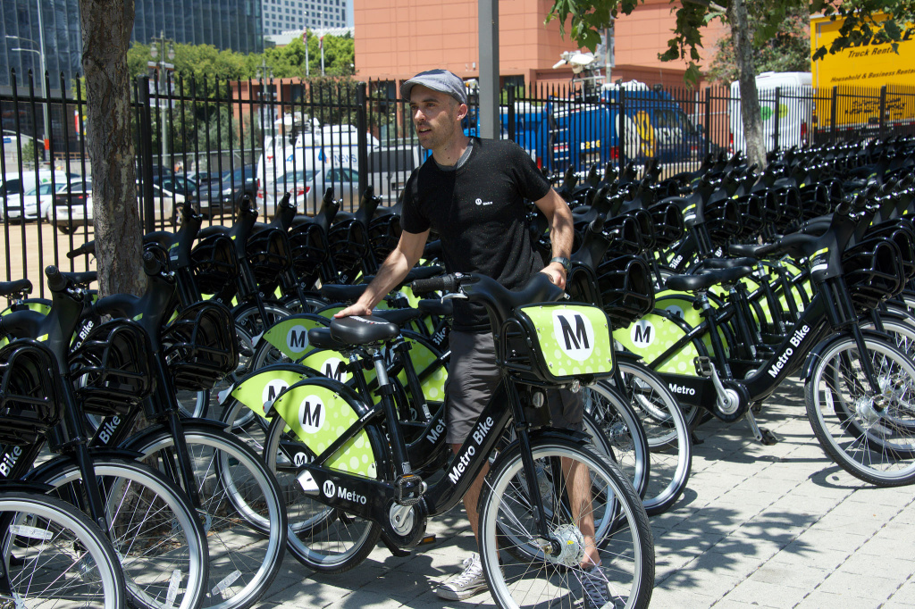 FILE: A rider checks out a bike share bicycle downtown.