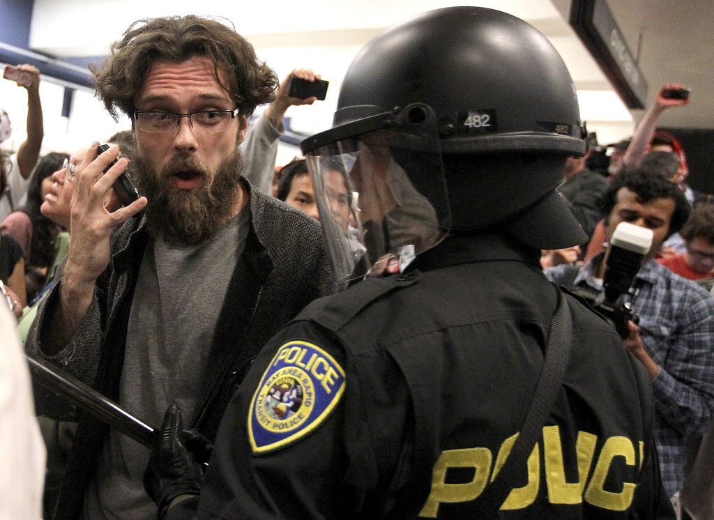 A protestor pretends to talk on a cell phone as he taunts a Bay Area Rapid Transit (BART) police officer at the Civic Center station on August 15, 2011 in San Francisco, California.