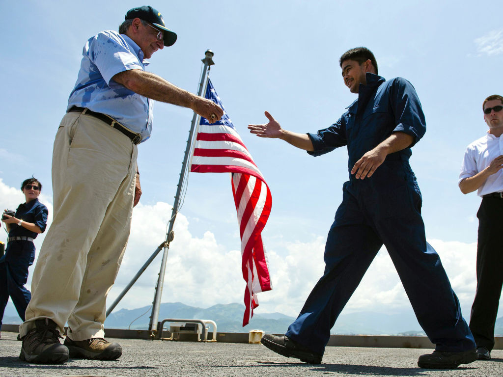 U.S. Defense Secretary Leon Panetta hands out coins to members of the crew as he visits USNS Richard E. Byrd in Cam Ranh Bay, Vietnam, on Sunday.