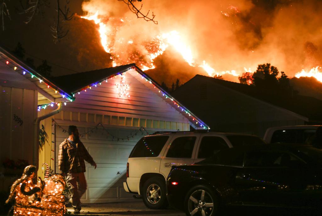 A man prepares to evacuate his home as a wildfire burns along a hillside near homes in Santa Paula, California, on December 5, 2017.