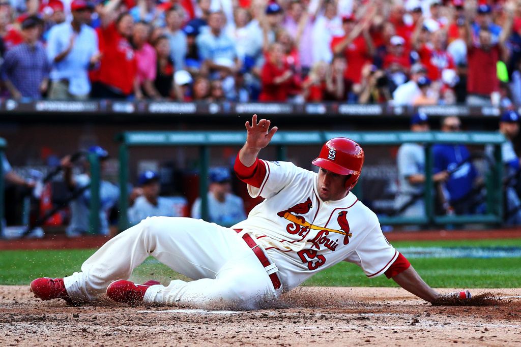 David Freese #23 of the St. Louis Cardinals slides into home plate to score the first run of the game on a sacrifice fly hit by Jon Jay #19 in the fifth inning against the Los Angeles Dodgers during Game Two of the National League Championship Series at Busch Stadium on Oct. 12, 2013 in St Louis, Missouri.