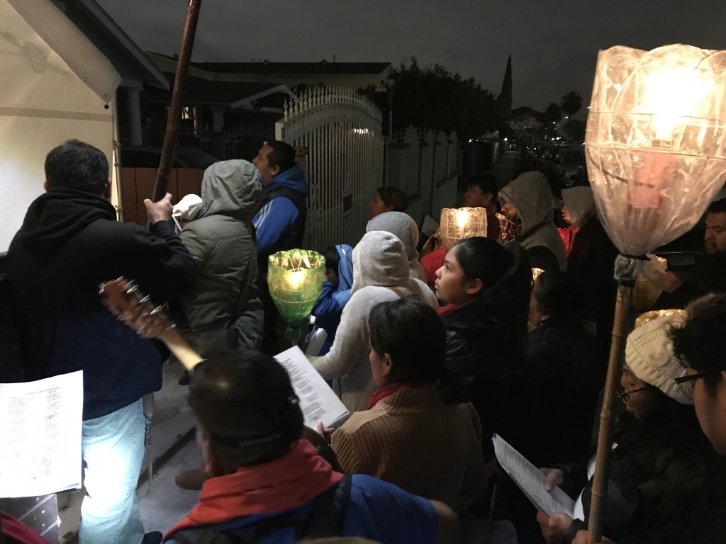 "A group in South LA, organized by ""Peregrinos Unidos en Familia"" – Pilgrims United in Family - participates in the annual Posada, recreating the journey of Mary and Joseph as they searched for shelter on the eve of Jesus's birth."