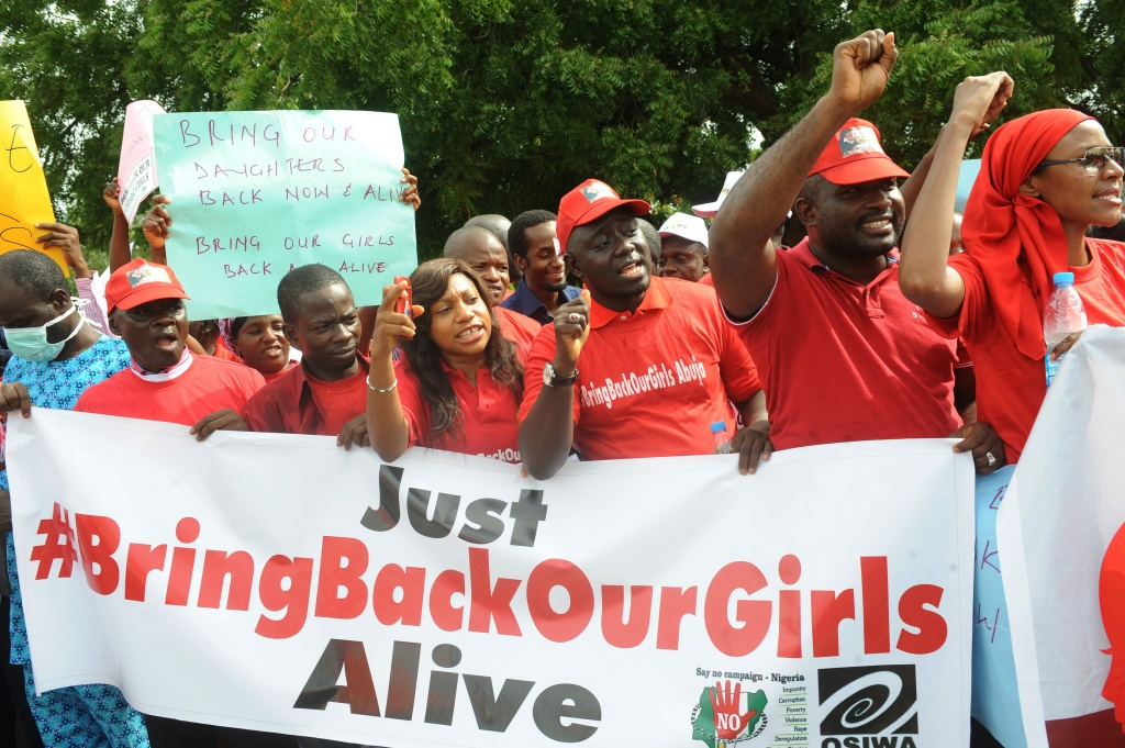 Caption: Members of civil society groups shout slogans to protest the abduction of Chibok school girls during a rally pressing for the girls' release in Abuja on May 6, 2014, ahead of World Economic Forum. AFP PHOTO/PIUS UTOMI EKPEI