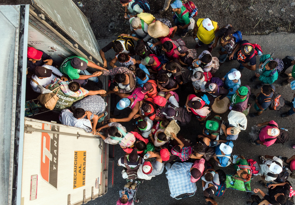 Honduran migrants taking part in a caravan heading to the US, get on a truck, near Pijijiapan, southern Mexico on October 26, 2018.