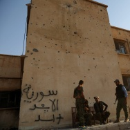 TOPSHOT - Kurdish fighters belonging to the police force -- the Asayesh -- and the People's Protection Units (YPG) stand in front of a building covered in bullet holes in the northeastern Syrian city of Hasakeh on August 23, 2016.