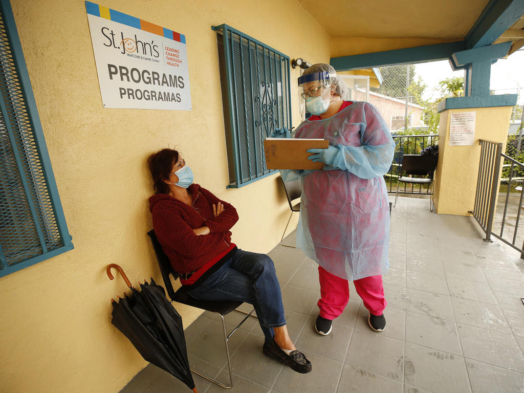 Maria Banderas, left, answers questions from medical assistant Dolores Becerra on May 18 before getting a coronavirus test at St. Johns Well Child and Family Center in South Los Angeles, one of the LA neighborhoods hit hard by COVID-19.