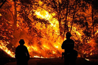 Los Angeles County fire fighters Pat Dunham (L) and Steve Bermau look on as the out of control Station Fire threatens a home on near Ocean View Drive in the La Canada Flintridge foothills above Los Angeles on August 29, 2009 in Los Angeles, California.