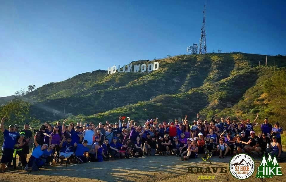 Hikers pose for a photo in front of the Hollywood sign.
