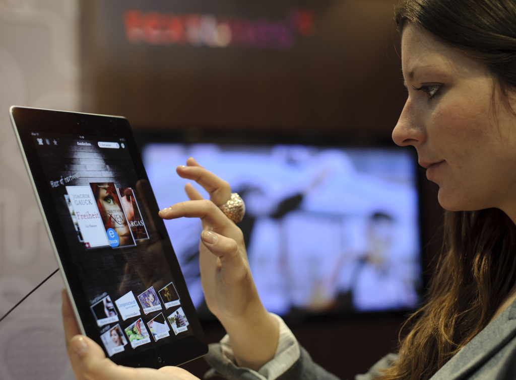 A fair goer tries out the textunes eBook reader app on an Apple iPad at the Leipzig Book Fair on March 15, 2012 on the fairgrounds in Leipzig, eastern Germany