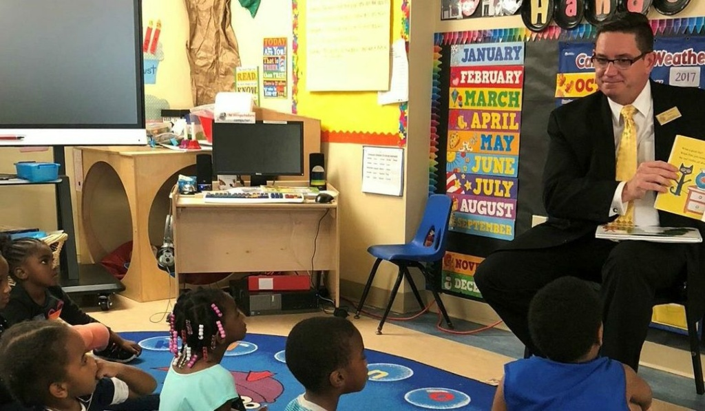 Bobby Cagle (right) reads to a group of children. Cagle is the new head of LA County's Department of Children and Family Services.