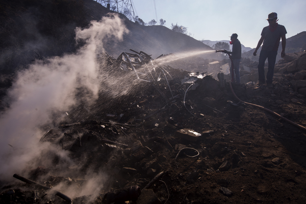 Ranch hands Angel Flores  and Anthony Martin (R) hose down smoldering property near stables where 29 horses were killed by the Creek Fire at Rancho Padilla on Dec. 6, 2017 near Sylmar, California.