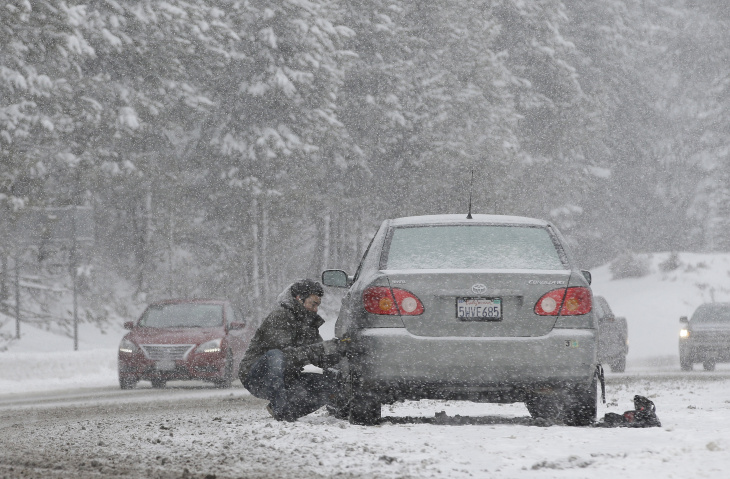 File: A motorist puts on snow chains near Echo Summit, Calif., Tuesday, Jan. 3, 2017.
