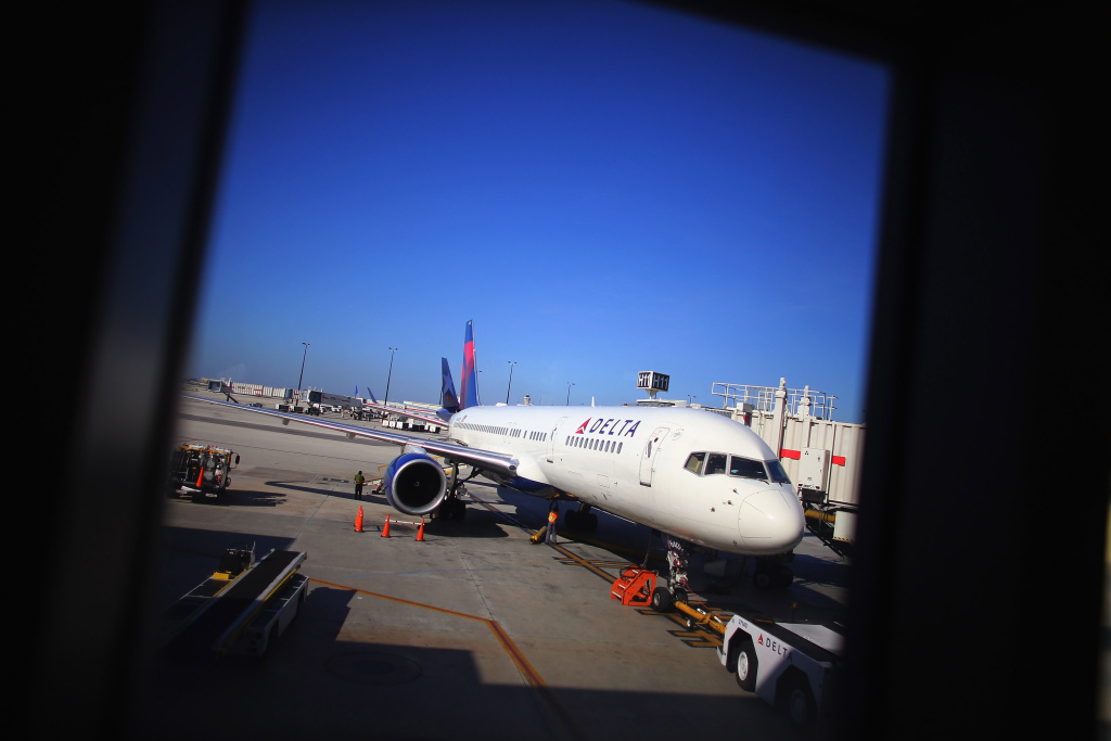 A Delta airlines plane is seen at the gate in LaGuardia Airport as passangers travel on the day before Thanksgiving on November 21, 2012 in New York, United States.