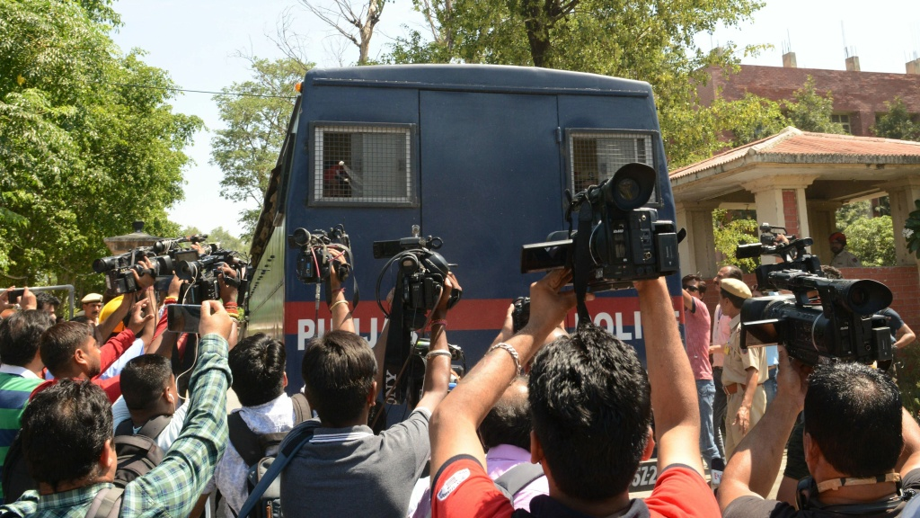 Journalists gather around an Indian police vehicle carrying seven people accused in the 2018 rape and murder of an 8-year-old girl in the state of Jammu and Kashmir. Six men were convicted and one was acquitted on Monday. Another suspect will be tried in juvenile court.