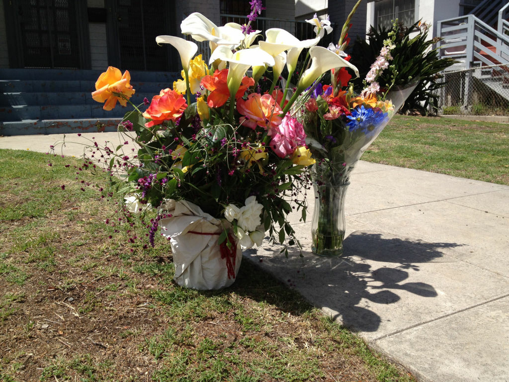 Neighbors and USC students placed flowers in front of the house the male victim tried to crawl to for help.