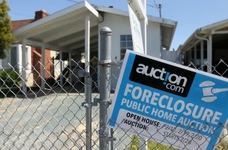 A foreclosure sign hangs on a fence in front of a foreclosed home on in Richmond, California.