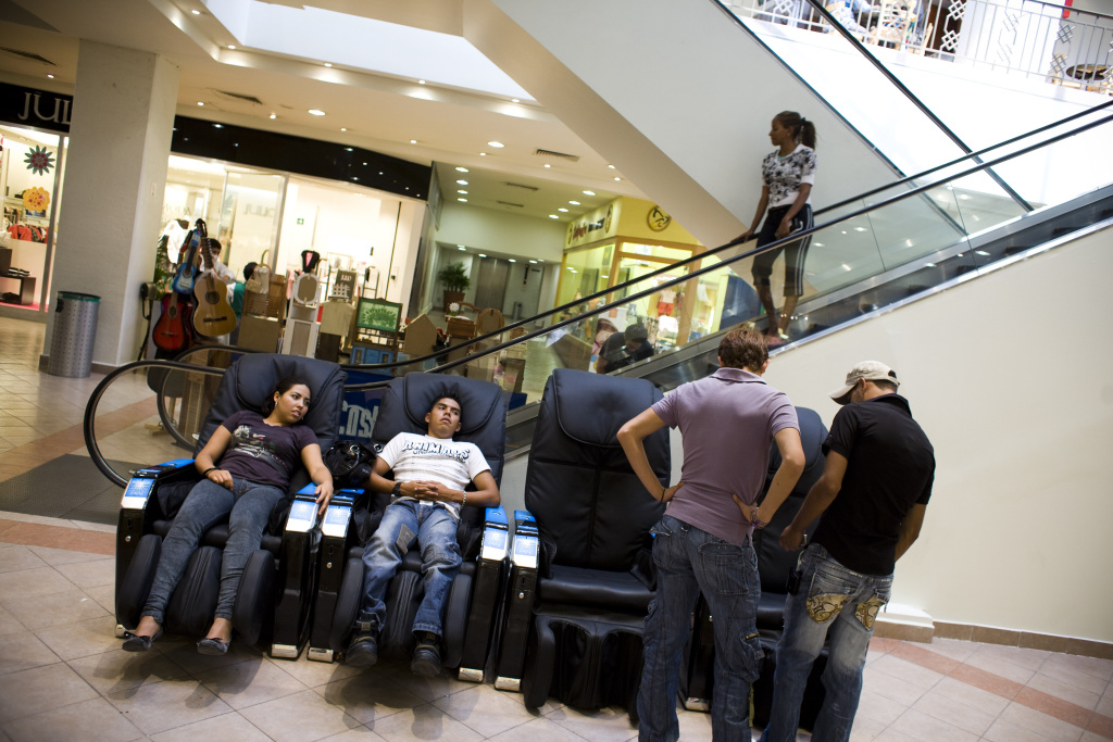 People sit in vibrating massage chairs in a mall in Mexico City, Mexico.