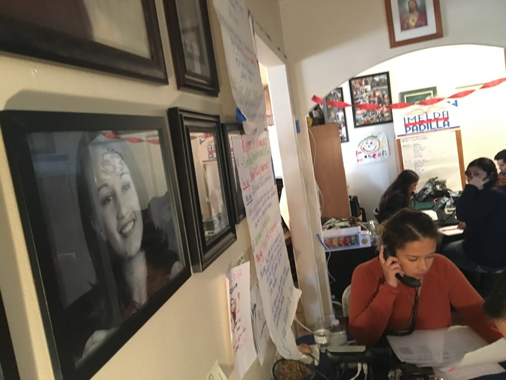 Carolina Salguero, bottom right, a volunteer for L.A. school board candidate Imelda Padilla, makes a campaign phone call in the campaign's headquarters in Padilla's childhood home in Pacoima. Family photos of the candidate, left, and her siblings cover the walls of the living room.
