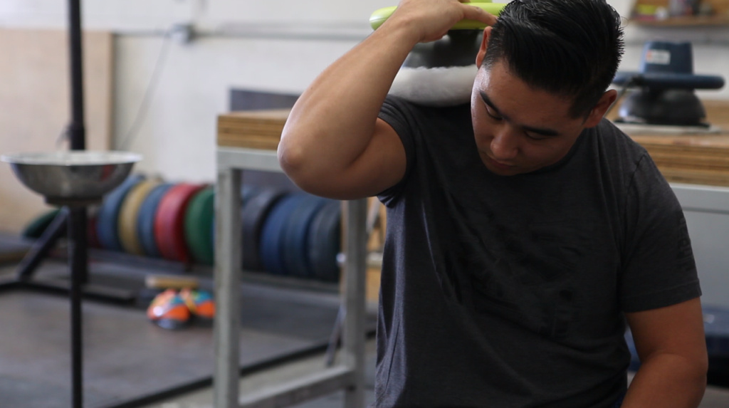 Weightlifting coach Sam Chang uses a car buffer on his shoulders at Waxman's Gym in Lawndale in October 2017.