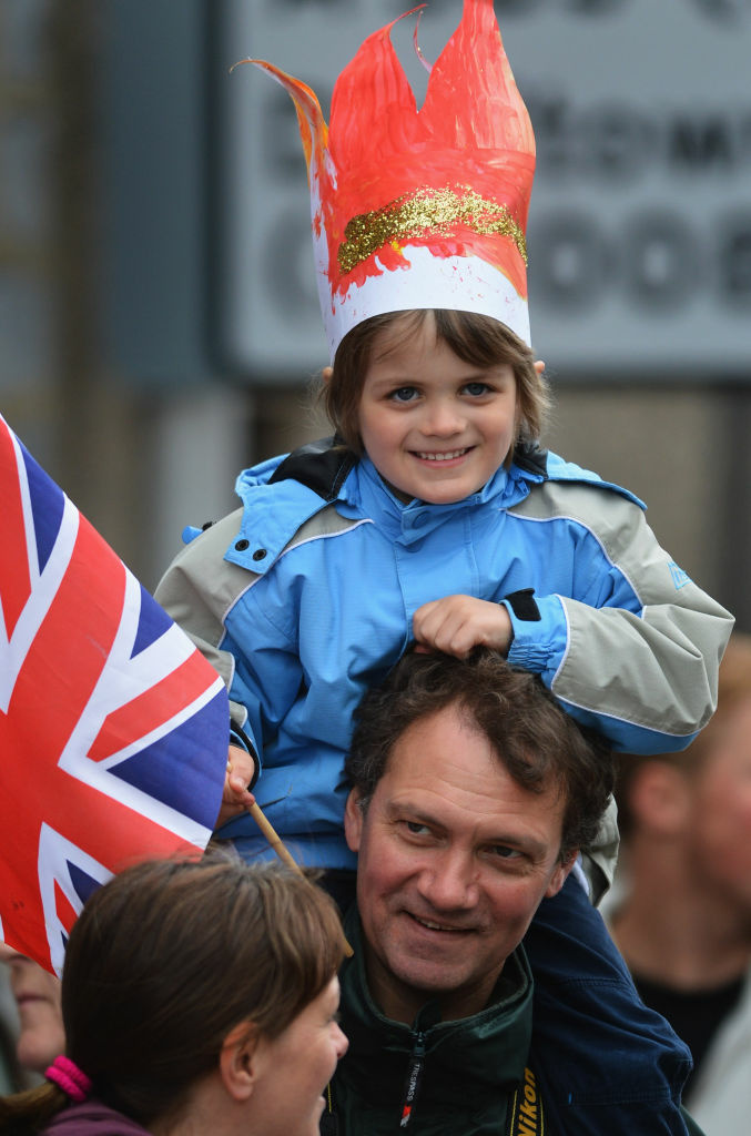 A child on a man's shoulders awaits the arrival of the Olympic Torch on June 11, 2012 in Tomintoul, Scotland.