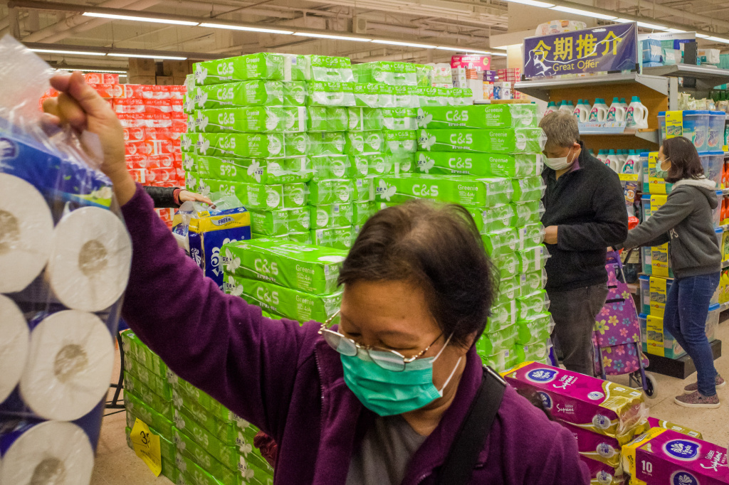 Shoppers wearing a face mask buying toilet papers in a supermarket.