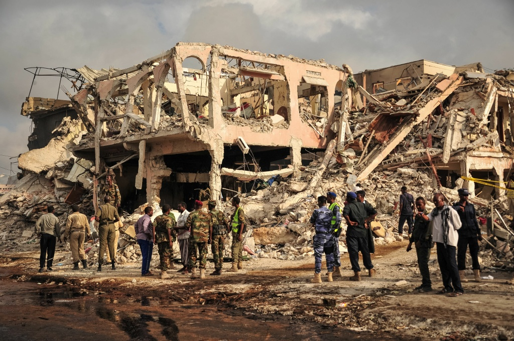 Somali security officers patrol the scene where a truck bomb exploded in the center of Mogadishu on October 15, 2017.