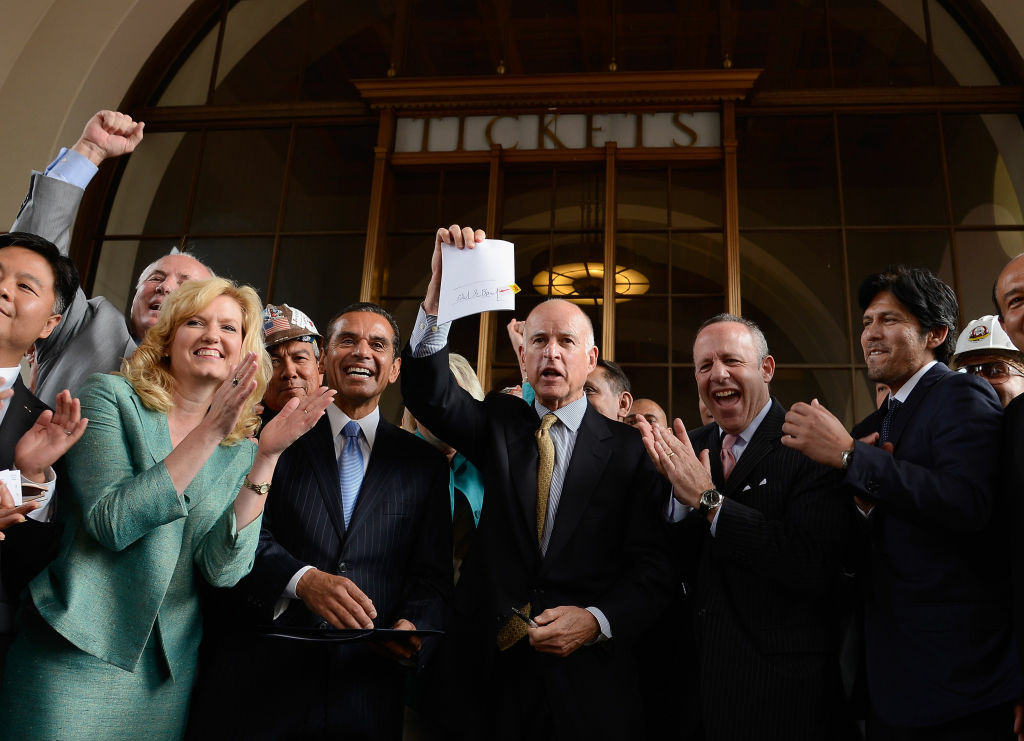 CA Gov. Jerry Brownholds up a legislation which he signed authorizing initial construction of California's $68 billion high-speed rail line.