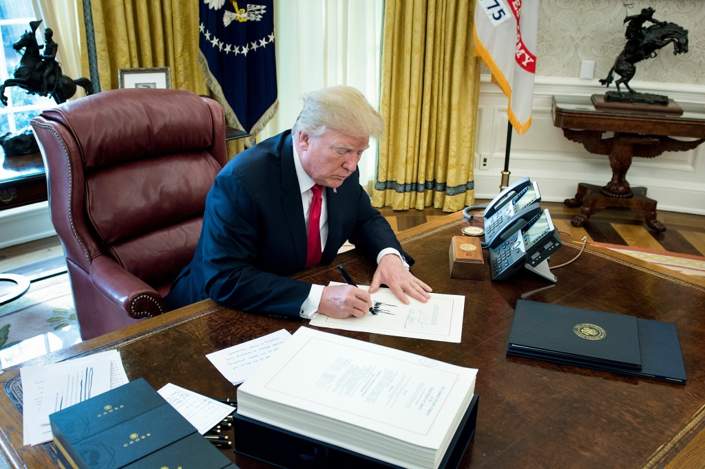 United States President Donald J. Trump signs the Tax Cut and Reform Bill in the Oval Office at The White House in Washington, DC on December 22, 2017.