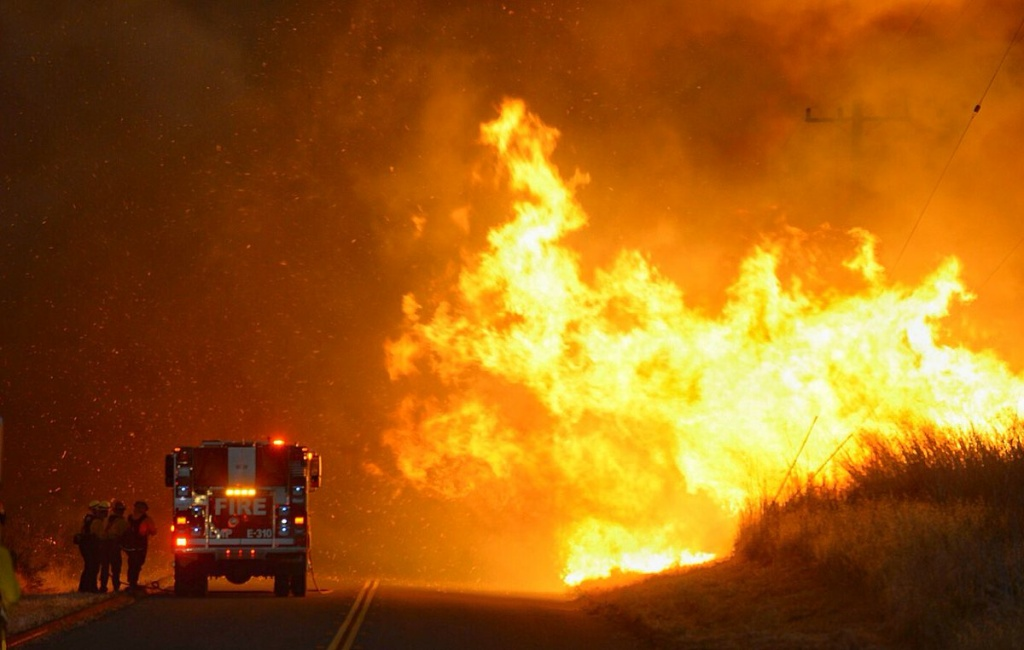 Firefighters take shelter behind the engine as flames advance on them along near El Capitan State Beach on Thursday, June 16, 2016.