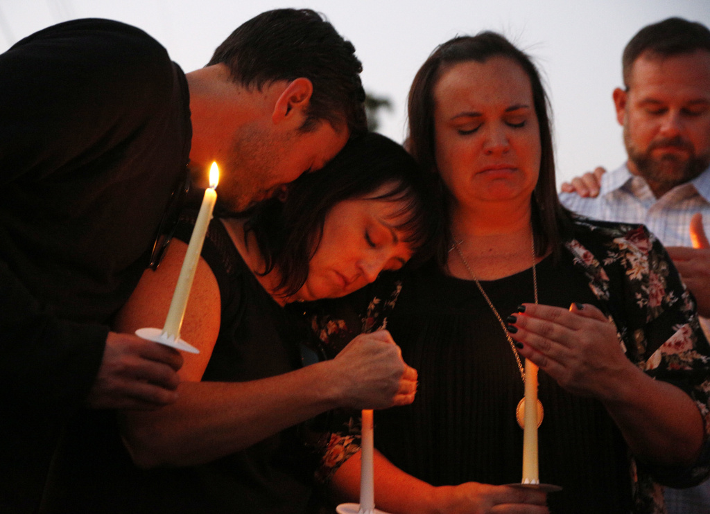 From left, Ryan Donato, Heather Barclay and her sister Tracy Gyurina grieve at a candlelight vigil for Nicol Kimura, a victim of the Las Vegas mass shooting, at Sierra Vista Elementary School in Placentia, Calif., Sunday, Oct. 8, 2017.