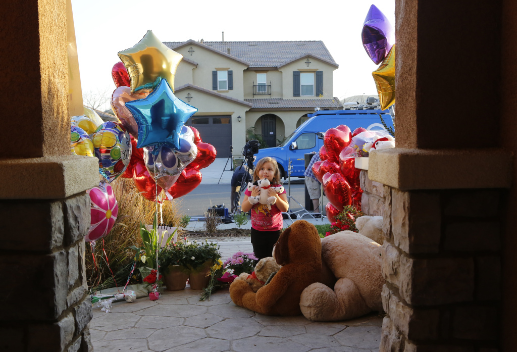 File: Neighbor Rilee Unger, 3, plays with a toy after dropping off a couple of her own teddy bears on the porch of a home where police arrested a couple on Sunday accused of holding 13 children captive in Perris, Calif., Thursday, Jan. 18, 2018.