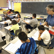 Teacher Arlene Lebowitz assists a student in her third-grade class during summer school July 2, 2003 in Chicago, Illinois.