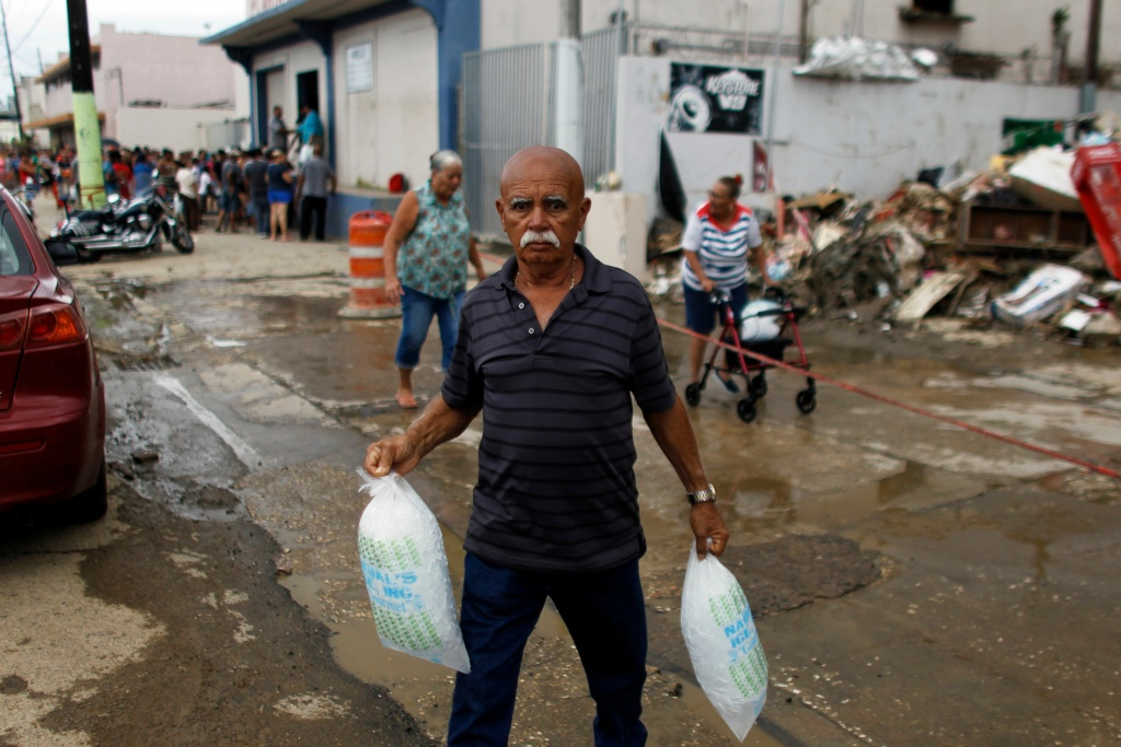 A man carries two bags of ice he bought at a local ice plant in the aftermath of Hurricane Maria, in Arecibo, Puerto Rico, September 30, 2017.