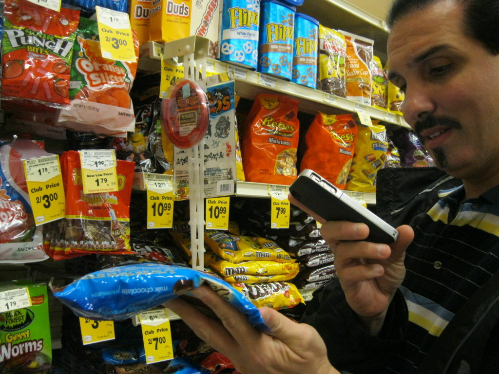 Julian Vargas, who is legally blind, uses his iPhone to scan the bar code on a package in the grocery store.  The phone then reads him information about the product.